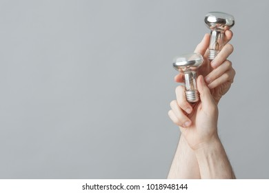 Saving energy concept. Young man's hands holding glass lamps over light grey background. Close up. Copy-space. Studio shot