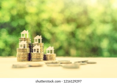Saving for a first house deposit or a first time home buyer program concept : House models on stacks of coins, depicts saving for a down payment on a real estate or tangible / non depreciation assets
