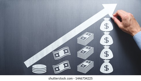 Saving and growing money concept. Businessman drawing money and arrow on chalkboard.