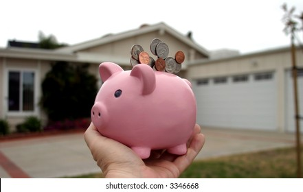 Saving for a home concept pink piggy bank in front of a house