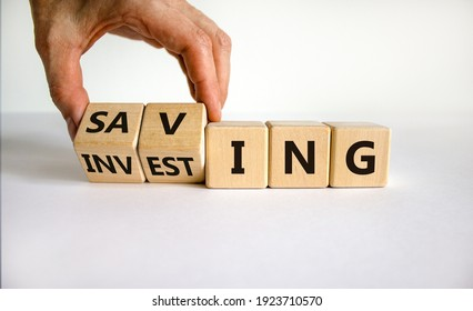 Saving or investing symbol. Businessman turns cubes and changes the word 'investing' to 'saving'. Beautiful white table, white background, copy space. Business and saving or investing concept.