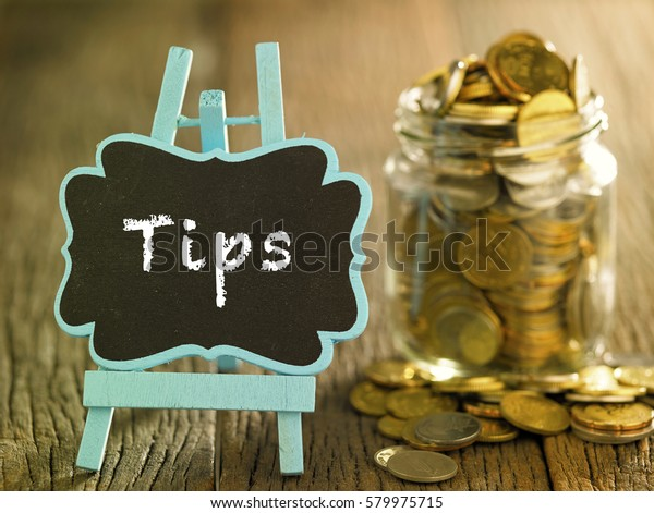 saving jar full of coin and a mini blackboard with text-tips