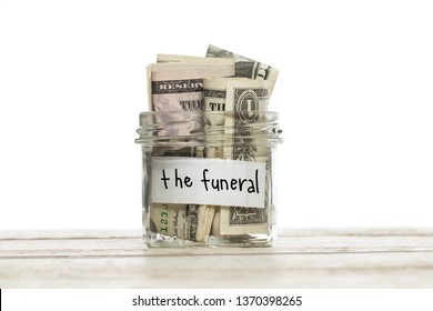 Saving jar with money for the funeral on white wooden table isolated