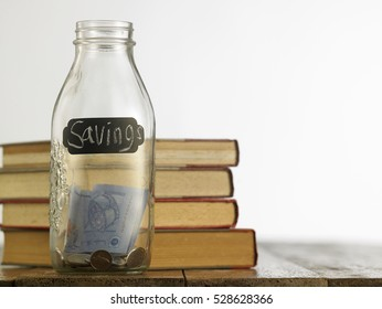 saving jar with stack of books on the wooden table