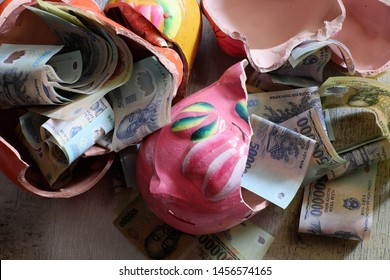 Saving money from broken piggy bank after long time to save up for emergency situation or retirement planning or buy house, many Vietnamese dong banknote on wooden background