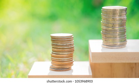 Saving money and business  concept. Gold and silver money coin stack step growing growth  saving money with over blurred abstract nature lights and greenery  background.