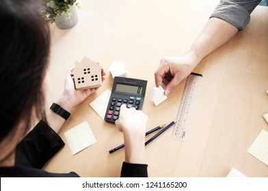 Saving money for buy a new house or loan for plan business investment of real estate concept. Blur Woman hand hold a home model with calculate for housing loans. Banks approve loans to buy homes.