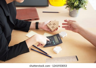 Saving money for buy a new house or loan for plan business investment of real estate concept. Woman hand hold a home model with calculate for housing loans. Banks approve loans to buy homes.