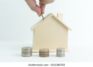 Saving money, coins and model houses on a white background