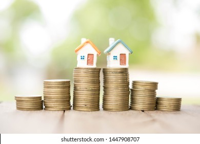 Saving money concept, coin stack growing business, save money for investment. coins to buy a home concept concept for property ladder. A small house on a pile of coins And have a financial chart.