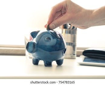 Saving money concept, hand with a coin and a piggy bank on an office table, selective focus on the coin