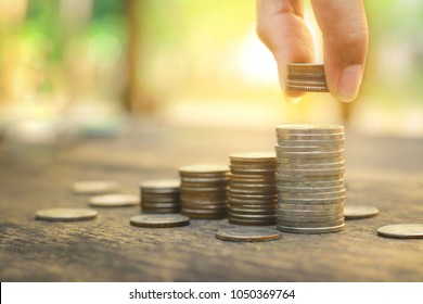 Saving money concept with Hand putting money coin stack growing business on abstract sunset background