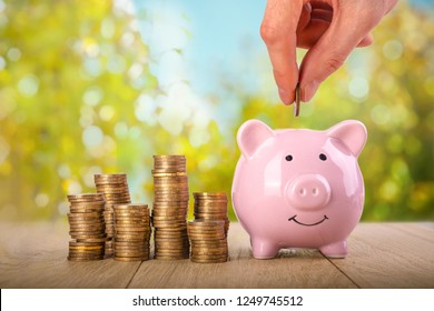 saving money concept with hand putting coin into piggy bank with stack of coins