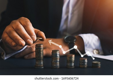 Saving money concept. Hand putting money coin stack with  growing business graph.