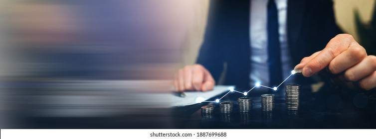 Saving money concept. Hand putting money coin stack with  growing business graph. Panoramic business banner with  copy space. - Shutterstock ID 1887699688