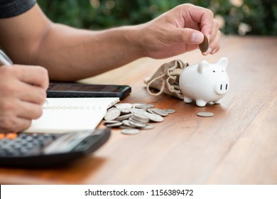 Saving money concept Man hand putting coin on piggy bank and write Finance.save money concept.