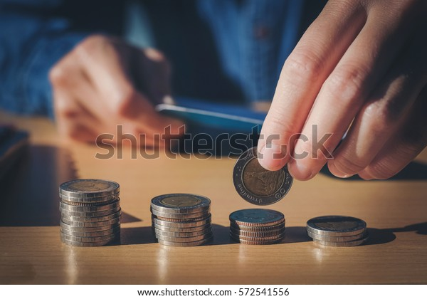 Saving money concept Man hand putting Row and coin stack growing business
