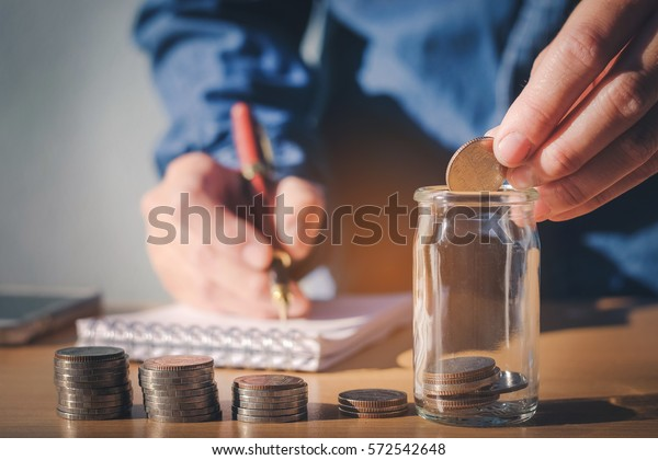 Saving money concept Man hand putting Row and coin Write Finance