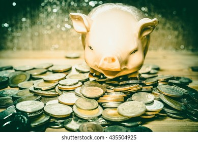 Saving money concept, Many coin and Piggy Bank. Save money with stack money coin for growing your business. Piggy bank on a pile of coins. - Vintage tone.