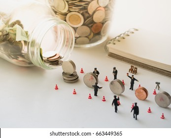 saving money concept with miniature police officer directing traffic of coins stack go to the glass, business and financial concept, bank and Accounting concept,