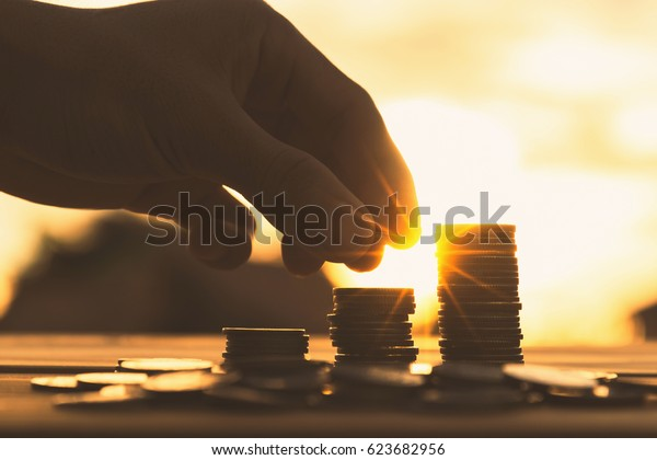 Saving money concept preset by Male hand putting money coin stack growing business.