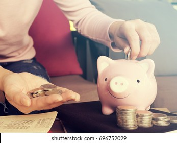 Saving money concept.Close up hand putting coin into piggy bank for saving money.young smart woman holding money coin and prepare to put the coin in piggy bank.