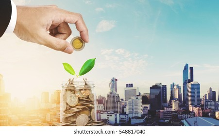 Saving money concepts, businessman hand putting coin in glass jar, with plant growing, city in sunrise background