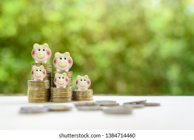 Saving money, financial concept : Piggy bank on rows of coins, depicts amount of money left over after spending and invest in unit trust, mutual fund or bond market for higher interest with low risk