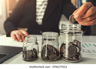saving money with hand putting coins in jug glass concept financial - Shutterstock ID 1936175311