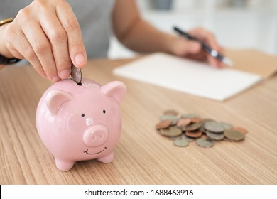 saving money and home finance.young women put money coin in piggy bank and record the expenses.