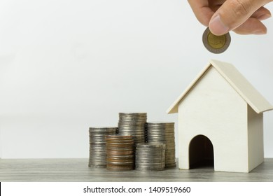 Saving money, home loan, mortgage, a property investment for future concept. A man hand putting coin over small residence house and money bag on white background and space. A sustainable investment.