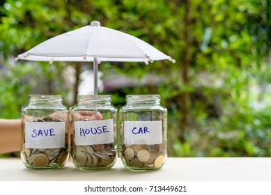 Saving money for house and car concept : Coins in jars under an umbrella. Ideas of saving for a down payment on a car or home that allow buyers to use down payment to reduce overall cost of borrowing.