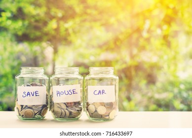 Saving money for house and car concept : Coins in three jars with label. Ideas of saving for a down payment on a car or home that allow buyers to use down payment to reduce overall cost of borrowing.