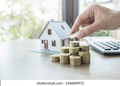 Saving money for house and real estate. Woman hand protecting on stack coins and house model on table.