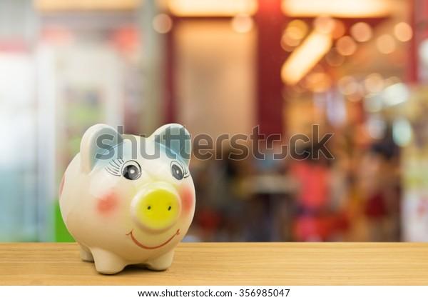 saving money in piggy bank on wooden background over bokeh light in restaurant,concept saving money