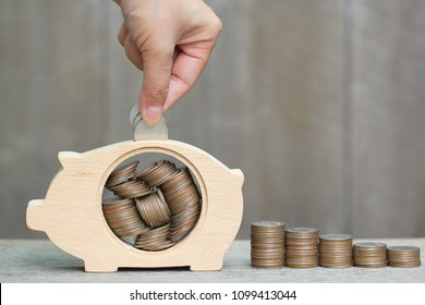 Saving money for prepare in future concept, Woman hand putting a coin into piggy bank wood on wooder background