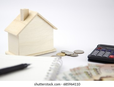 Saving money for real estate concept, House model, piles of coins and calculator calculate for pay loan.