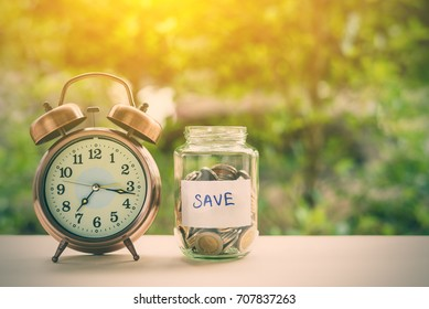 Saving money for sustainable life in the future concept : Coins in a clear glass jar with vintage clock nearby. Saving is money saved for education, paying taxes, insurance, health, travel and more ..
