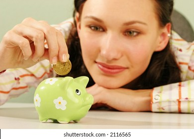 saving money-young woman putting a coin into a green money-box-close up