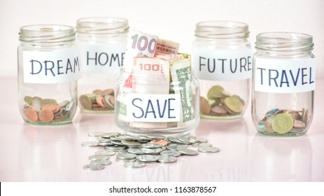 Saving plan for money for the future of life. Concept of investments. Difference group of money in glass jar on table desk. Financial planning. Deposit photo. Banknotes and coins.