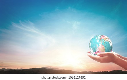 Saving planet earth concept: Human hands holding globe on mountain sunset background. Elements of this image furnished by NASA
