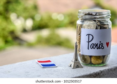 Saving planing for travel to France budget of holiday concept, stack of coins money in the glass bottle with flag of France and Eiffel Tower model. Financial concept.
