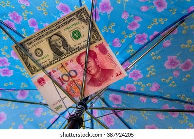 Saving for a rainy day concept, bank notes under a colorful umbrella.