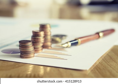 Saving stack coins money concept,graph,chart  document and pen on desktop desk in hipster office,copy space.selective focus,vintage color