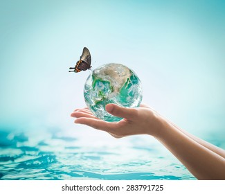 Saving water, world water day, environmental ecology protection, earth day concept with woman's hand holding green planet on blur sea or ocean background. Element of this image furnished by NASA