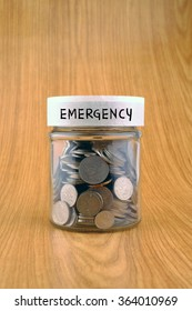 savings concept, coins in jar with emergency label on wooden background.