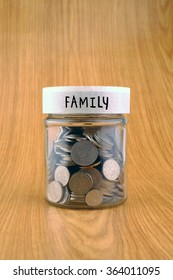 savings concept, coins in jar with family label on wooden background.