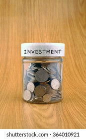 savings concept, coins in jar with investment label on wooden background.