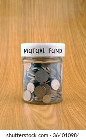 savings concept, coins in jar with mutual fund label on wooden background.