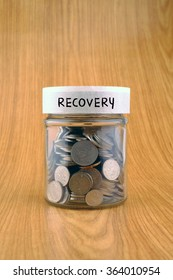 savings concept, coins in jar with recovery label on wooden background.